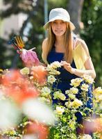lachende jonge vrouw in uniform op tuinieren tuin foto