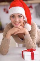 lachende jonge vrouw in de keuken, geïsoleerd op Kerst achtergrond foto