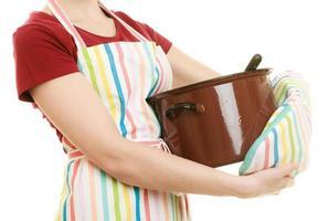 huisvrouw chef-kok keukenschort met pot soep en pollepel foto