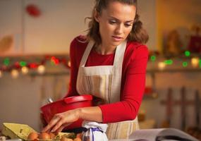 jonge huisvrouw die Kerstmisdiner in keuken voorbereidt