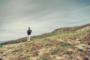 wandelaar man lopen in de bergen foto