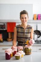 gelukkige jonge huisvrouw met potten van ingemaakte groenten