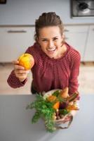 close-up op jonge huisvrouw die verse appel van lokale markt toont