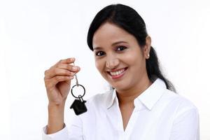 vrolijke zakenvrouw huissleutel houden foto