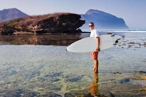 surfer met surfboard op een kustlijn foto