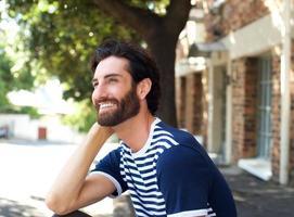 vrolijke jonge man buiten zitten foto