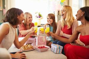 vrienden die een toost met sinaasappelsap maken bij baby shower foto