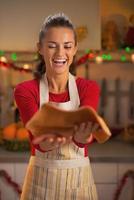 gelukkige jonge huisvrouw overgeven deeg voor kerstkoekjes foto