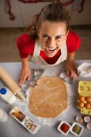 moderne huisvrouw die koekjes met kerstthema in de keuken maakt foto
