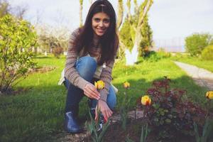 vrolijke vrouw die de bloemen snijdt foto