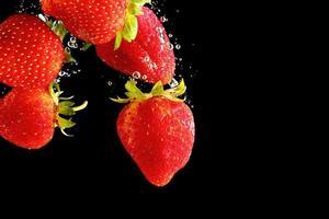 aardbeien in het water vallen op zwarte achtergrond foto