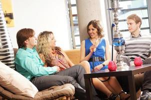 vier jongeren die een feestje hebben in de bar foto