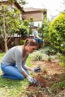 jonge vrouw en man aan het werk in de tuin foto