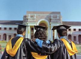 team van studenten kijken naar hun universiteit in afstuderen jurk.