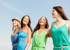 lachende meisjes lopen op het strand foto