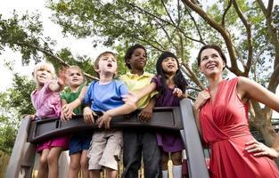 voorschoolse leraar met studenten op speelplaats uitkijken foto