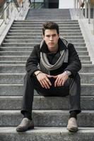 trendy knappe jongeman zittend op een lange trap buiten foto