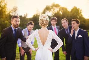 bruidsjonkers kijken naar bruid foto