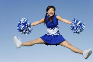 cheerleader die gejuich in de lucht uitvoert foto