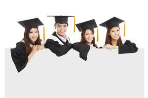 vrolijke jonge afgestudeerde studenten steken de hand op