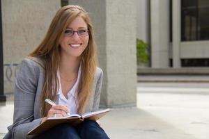 vrolijke, aantrekkelijke jonge vrouw met dagboek foto