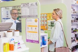 apotheker die met vrolijke jonge klant spreekt foto