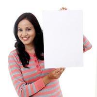 vrolijke jonge vrouw met leeg wit bord foto