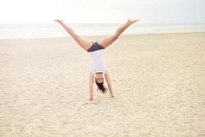 vrolijke vrouw op het strand dat handstand doet foto