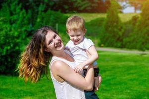 schattig vrolijk kind met moeder buiten spelen foto