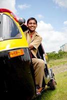 jonge vrolijke Indiase auto-riksja chauffeur foto