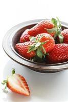verse aardbeien in kom, gehakte aardbeien op witte achtergrond foto