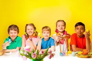vijf kinderen houden gekleurde paaseieren aan tafel