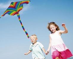 kinderen spelen vlieger geluk vrolijk strand zomer concept foto