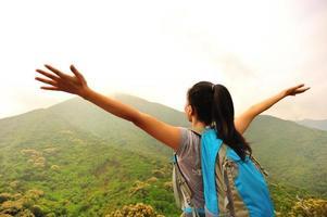 juichende wandelende vrouw open armen op bergtop foto