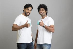 twee vrolijke jonge man met kopje thee foto