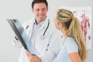 vrolijke arts die een patiënt iets op röntgenstraal toont foto
