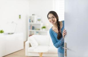 vrolijke vrouw die mensen uitnodigt om in huis binnen te gaan foto