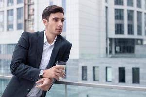 vrolijke jonge mannelijke werknemer is ontspannen op pauze foto