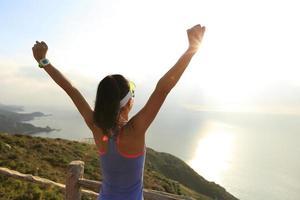 juichende jonge vrouw bij zonsopgang bergtop aan zee foto