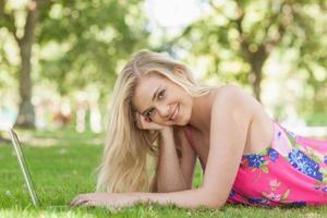 portret van vrolijke jonge vrouw met behulp van haar laptop foto