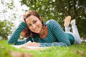 vrolijke toevallige student die op gras ligt dat een boek leest foto