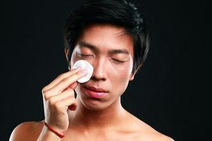 Aziatische man veegt zijn gezicht af met wattenschijfje foto