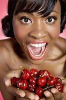 vrolijke jonge vrouw die kers in haar handen bekijkt foto