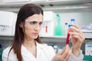 wetenschapper die een reageerbuis onderzoekt foto