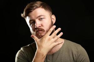 portret van knappe man met baard op zwarte achtergrond