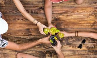 hand van mensen proost met alcoholcocktails foto
