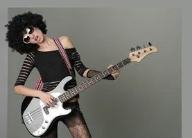 vrolijke meisje in pruik speelt op een gitaar foto