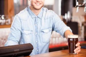 vrolijke jonge mannelijke barman dient klant in pub foto