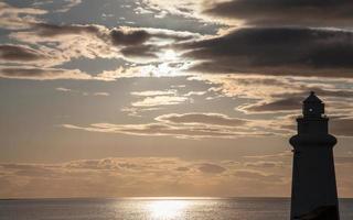 vuurtorensilhouet in humeurige zonsondergang foto