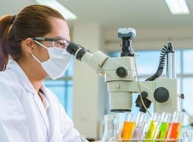 wetenschapper test dosering druppelbuis in het laboratorium foto